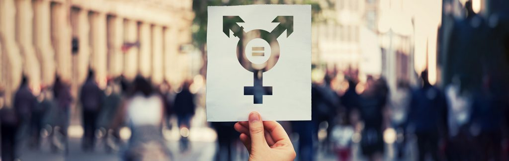 Hand holding a paper sheet with transgender symbol and equal sign inside. Equality between genders concept over a crowded city street background.