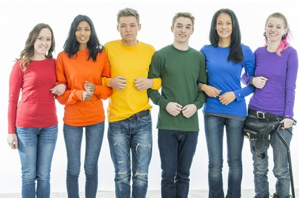 A multi-ethnic group of young people are standing in a row, with their arms linked together. They are wearing the colors of the rainbow for a gay pride concept.