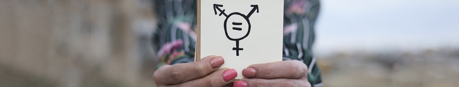 Closeup of hands holding a notepad with a transgender symbol drawn in it.