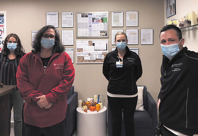 Members of the Center for Transgender Health staff hold signs in solidarity while wearing masks.