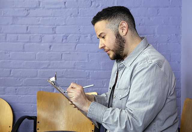 A transgender man sits in a waiting room, filling out paperwork on a clipboard.