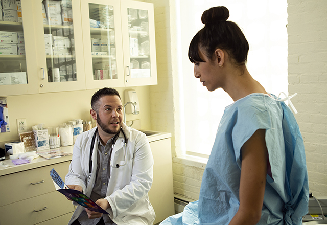 A transgender woman in a hospital gown speaking to her doctor.